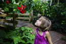 Girl making a face while looking at hibiscus in garden