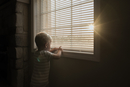 Boy playing with window blinds while standing at home