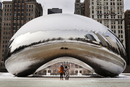 Rear view of tourists standing by snow covered Cloud Gate against buildings at Millennium Park