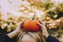 Cropped image of girl balancing pumpkin on head