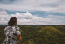 Rear view of man looking at Chocolate Hills while standing by railing against cloudy sky