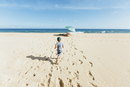 Rear view of boy running on sand while father and sister sitting at beach against sky during sunny day 11100085179| 写真素材・ストックフォト・画像・イラスト素材|アマナイメージズ