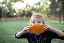 Portrait of girl holding carved pumpkin while standing in yard during Halloween
