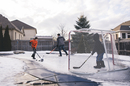 Father with sons playing ice hockey at yard against sky