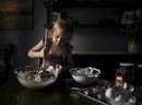 Girl mixing batter in bowl on table at home