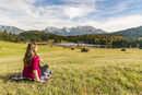 Woman sitting and staring at Gerold lake and Karwendel Alps, Krun, Upper Bavaria, Bavaria, Germany, Europe