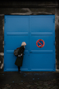 Full Length Side View Of Woman Puckering By Closed Blue Door