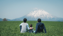 Rear View Of Family Looking At Mountain While Sitting On Grassy Field