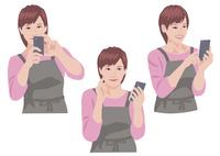 スマートフォンで写真を撮り、保存確認をするの主婦 10688000047| 写真素材・ストックフォト・画像・イラスト素材|アマナイメージズ