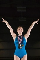 Female gymnastic medalist taking bow, portrait