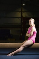 Female gymnast sitting on balance beam