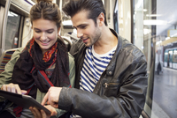 Young couple riding subway looking at digital tablet together 11001059808| 写真素材・ストックフォト・画像・イラスト素材|アマナイメージズ