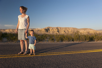Mother and toddler son walking together on paved road through desert 11001064480| 写真素材・ストックフォト・画像・イラスト素材|アマナイメージズ