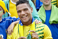 Brazilian football fan smiling cheerfully at match