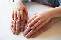 Hands of child and senior adult