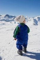 Young boy standing looking at mountains in snow 11015203309| 写真素材・ストックフォト・画像・イラスト素材|アマナイメージズ