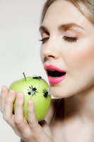 Young woman eating apple with flies on it