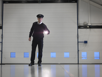 Security guard with torch in warehouse 11015220775| 写真素材・ストックフォト・画像・イラスト素材|アマナイメージズ