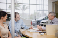Car salesman giving papers to couple