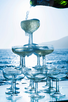 Champagne pouring into glasses with sea in background 11015228176| 写真素材・ストックフォト・画像・イラスト素材|アマナイメージズ