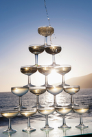 Champagne pouring into glasses with sea in background 11015228179| 写真素材・ストックフォト・画像・イラスト素材|アマナイメージズ