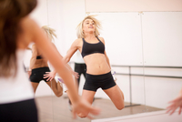 Young woman jumping in aerobics class