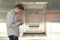 Mid adult man banking on cellphone next to bank deposit box