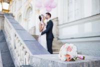 Mid adult bride and groom kissing on stairway 11015244487| 写真素材・ストックフォト・画像・イラスト素材|アマナイメージズ
