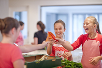 Teenage girls holding up chillies and carrot in kitchen 11015245984| 写真素材・ストックフォト・画像・イラスト素材|アマナイメージズ