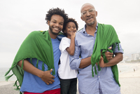 Mid adult man with father and son wrapped in Brazilian flag on Ipanema beach, Rio De Janeiro, Brazil