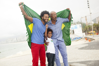 Mid adult man with father and son holding up Brazilian flag on Ipanema beach, Rio De Janeiro, Brazil