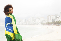 Portrait of young woman wrapped up in Brazilian flag on Ipanema beach, Rio De Janeiro, Brazil