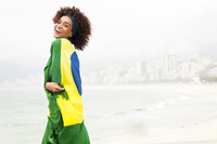 Portrait of young woman wrapped in Brazilian flag on Ipanema beach, Rio De Janeiro, Brazil