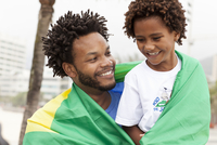 Father and son wrapped in Brazilian flag on Ipanema beach, Rio De Janeiro, Brazil