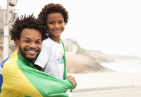 Portrait of father and son wrapped in Brazilian flag on Ipanema beach, Rio De Janeiro, Brazil
