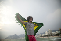 Smiling young man holding up Brazilian flag on Ipanema beach, Rio De Janeiro, Brazil