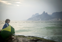 Young man wrapped in Brazilian flag sitting on rock, Ipanema beach, Rio De Janeiro, Brazil