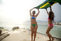 Portrait of two young women dancing whilst holding up Brazilian flag,  Ipanema beach, Rio De Janeiro, Brazil
