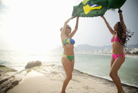 Two young women dancing whilst holding up Brazilian flag,  Ipanema beach, Rio De Janeiro, Brazil