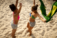 Overhead view of  two young women holding Brazilian flag whilst dancing, Ipanema beach, Rio De Janeiro, Brazil