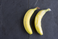 Still life of two bananas - one wrapped in plastic wrap 11015254643| 写真素材・ストックフォト・画像・イラスト素材|アマナイメージズ