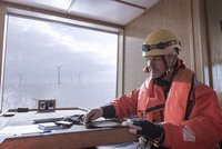 Engineer on boat making notes on digital tablet at offshore windfarm 11015255875| 写真素材・ストックフォト・画像・イラスト素材|アマナイメージズ