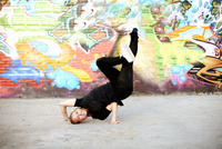 Young woman in upside down breakdancing freeze against graffiti