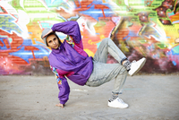 Young woman breakdancing freeze against graffiti