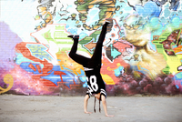 Young women in handstand breakdancing freeze against graffiti