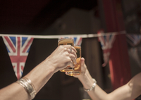 Detail of two female hands raising a toast with beer outside traditional pub