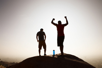 Two male friends, on top of mountain, in celebratory pose
