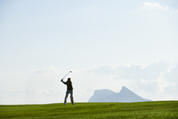 Golfer taking golf swing in front of mountain range