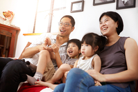 Young, modern Chinese family of parents and two young children sitting on sofa watching television together at home 11015266150| 写真素材・ストックフォト・画像・イラスト素材|アマナイメージズ