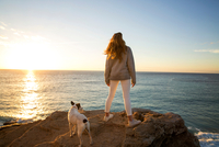 Rear view of woman and dog watching sunset from cliff rock, Conil de la Frontera, Spain 11015273390| 写真素材・ストックフォト・画像・イラスト素材|アマナイメージズ